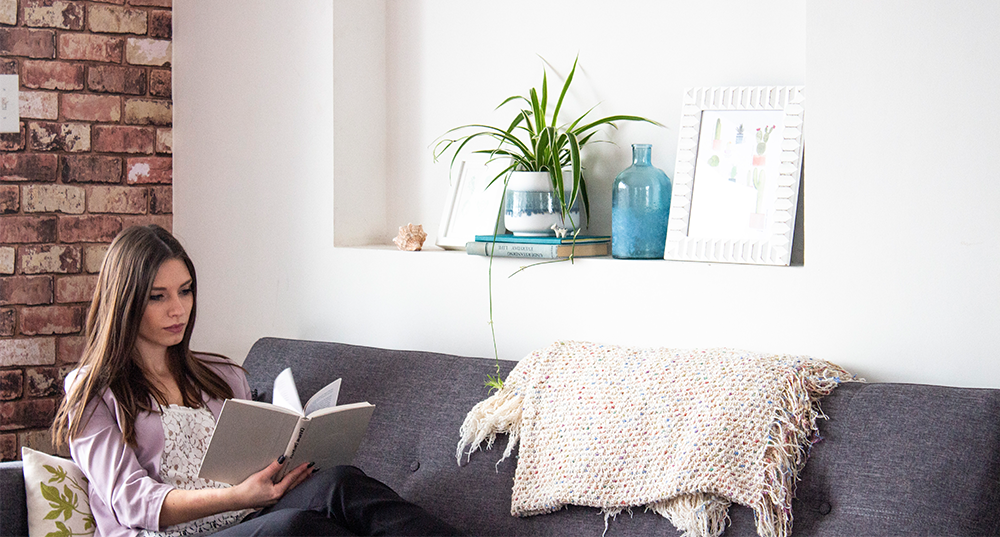 young woman reading book with plant shelfie behind